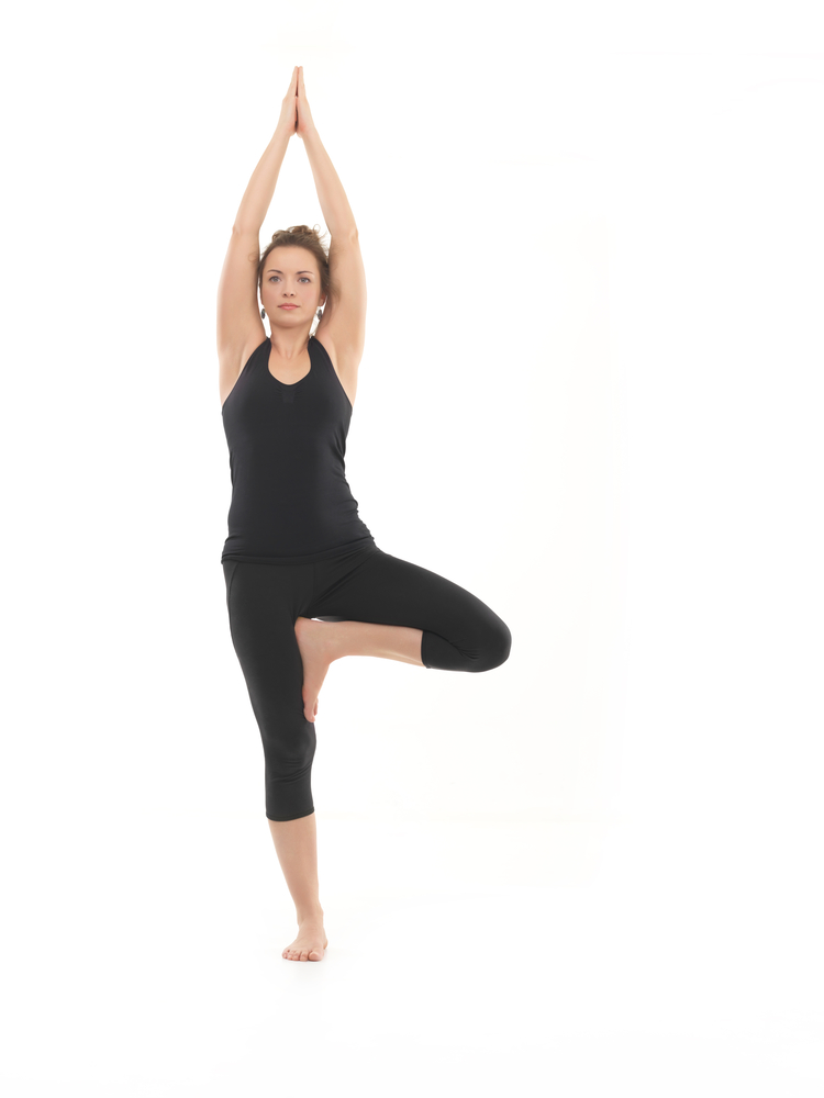 frntal view of young woman sitting in yoga posture, dressed in blak, on white background