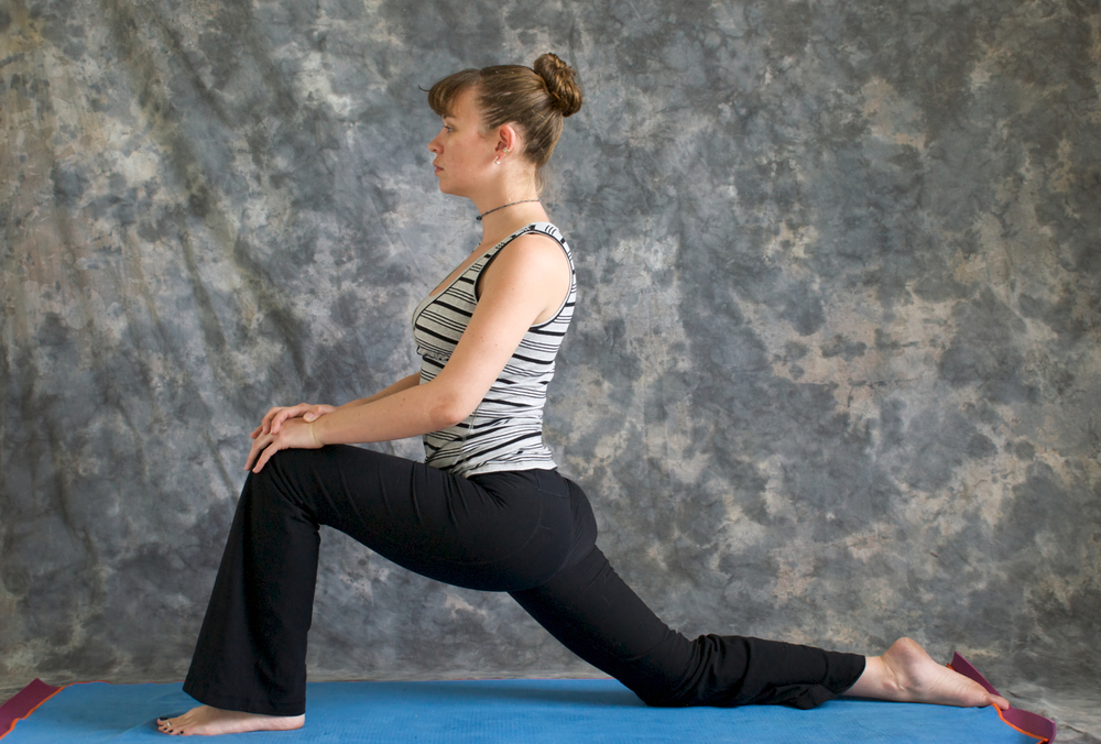 Young woman on yoga mat in woman doing Yoga posture Low Lunge or Ashwa Sanchalanasana with hands on knee, against a grey background in profile, facing left lit by diffused sunlight.